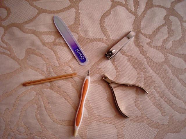 Herramientas de manicura: palito de naranjo, lima de vidrio, cortauñas, alicate y cortacutículas.  Imagen Venus y su espejo